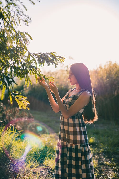 Woman in Black and White Plaid Dress Standing Near Green Plants