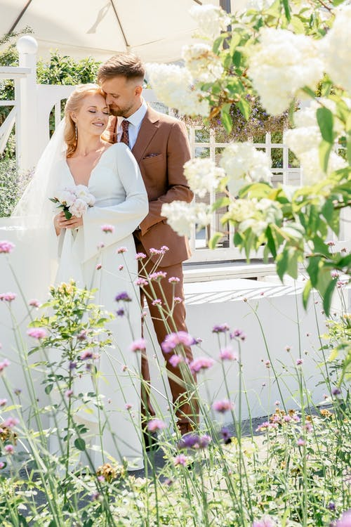 Man in Brown Suit and Woman in White Wedding Dress Standing on Flower Field