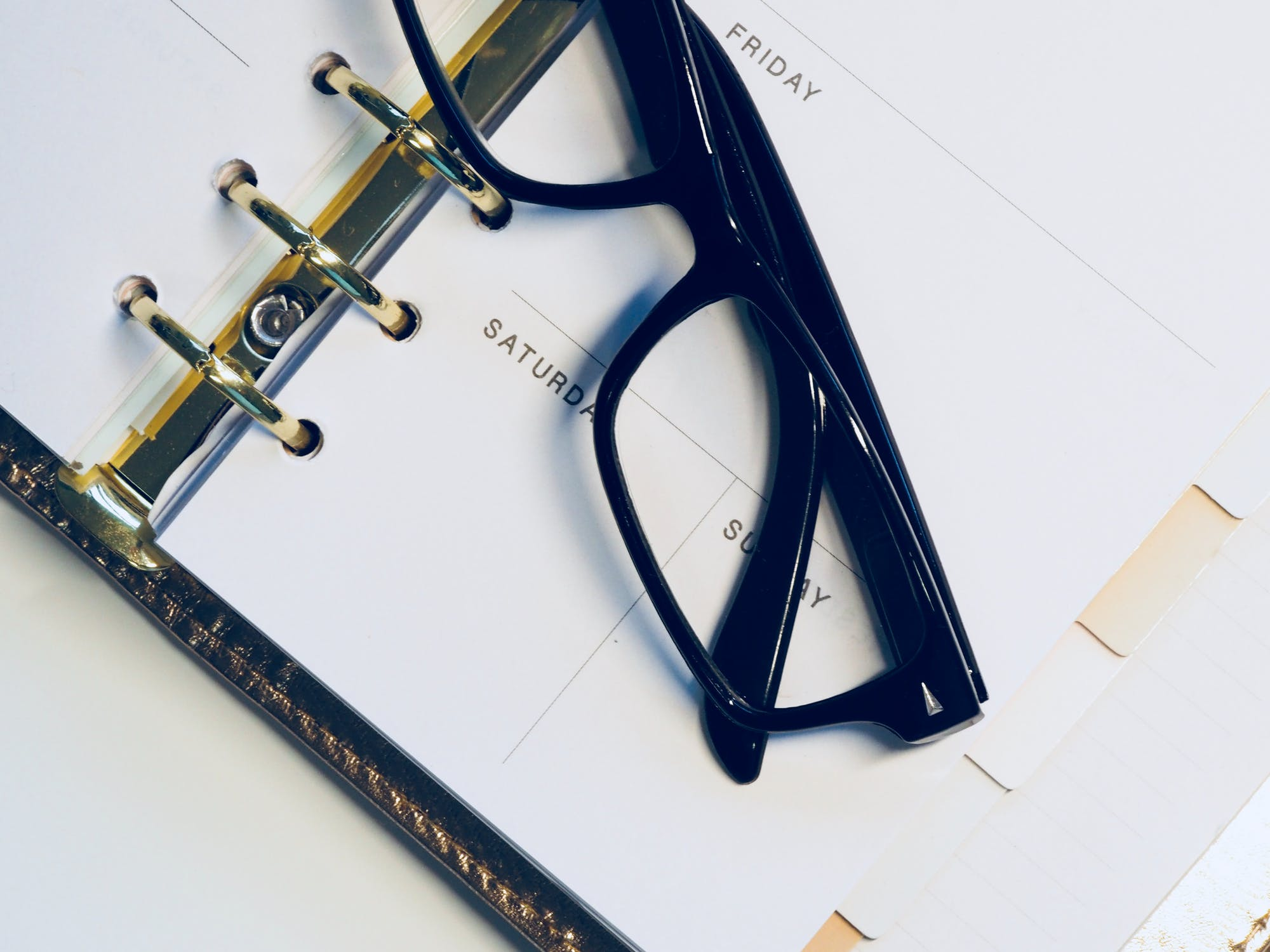 A daily planner sitting on a desk with a pair of black glasses on top