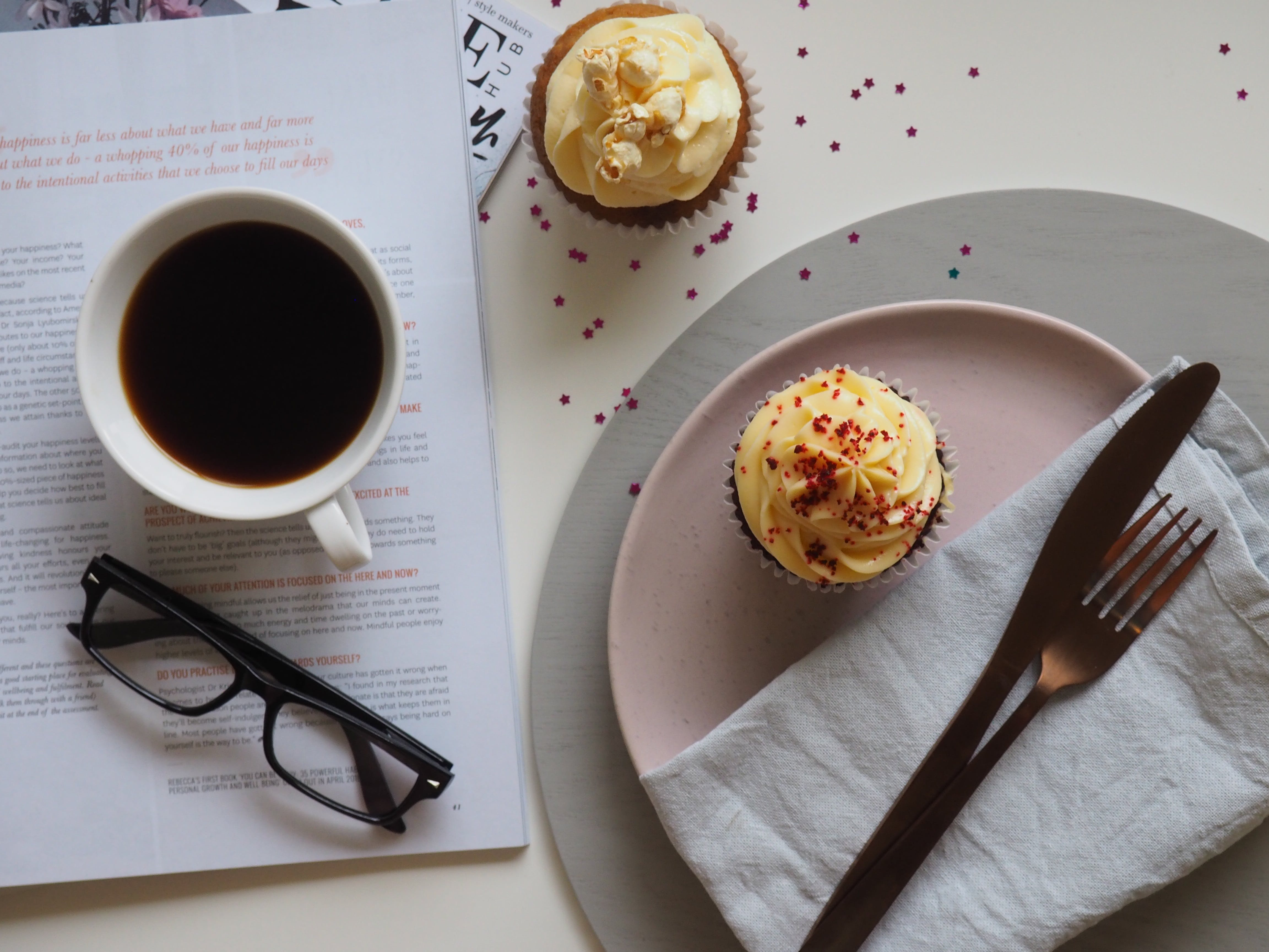 Top-view Photograph of Two Cupcakes, Cup, and Eyeglasses