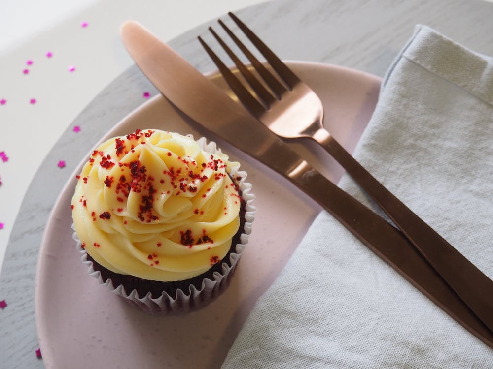 Silver Fork and Knife on Round Plate With Cupcake