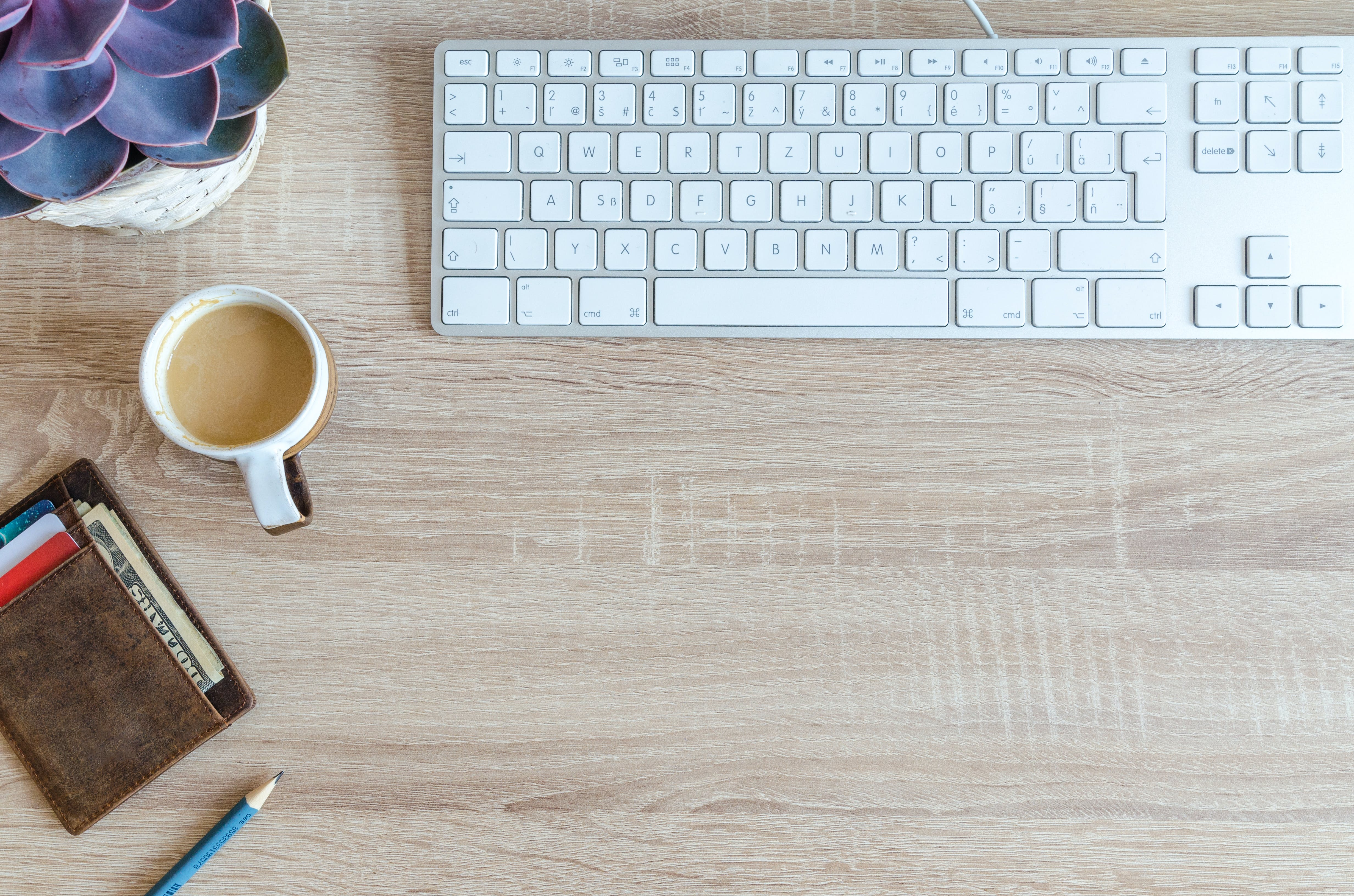 Cup of Coffee Near Keyboard on Table Top