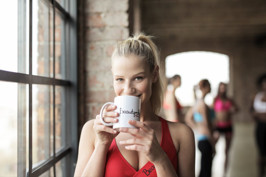 Woman in Red Scoop-neck Tank Top Holding White Mug