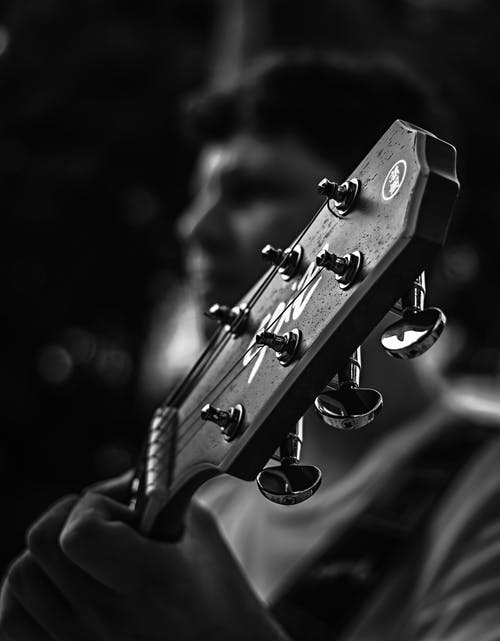 Person Playing Guitar in Grayscale