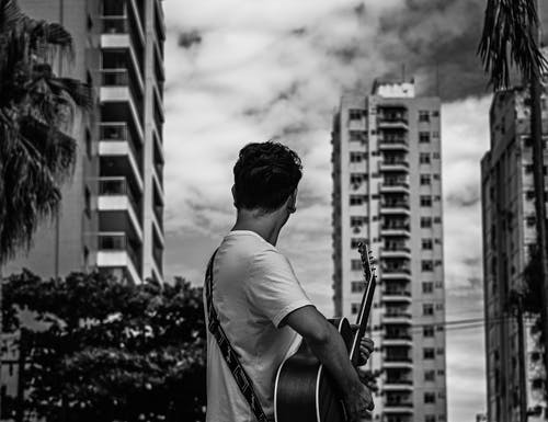 Man in White Shirt Playing Guitar