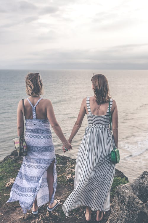 Two Women Wearing Sleeveless Dress Holding Each Others Hand on Cliff