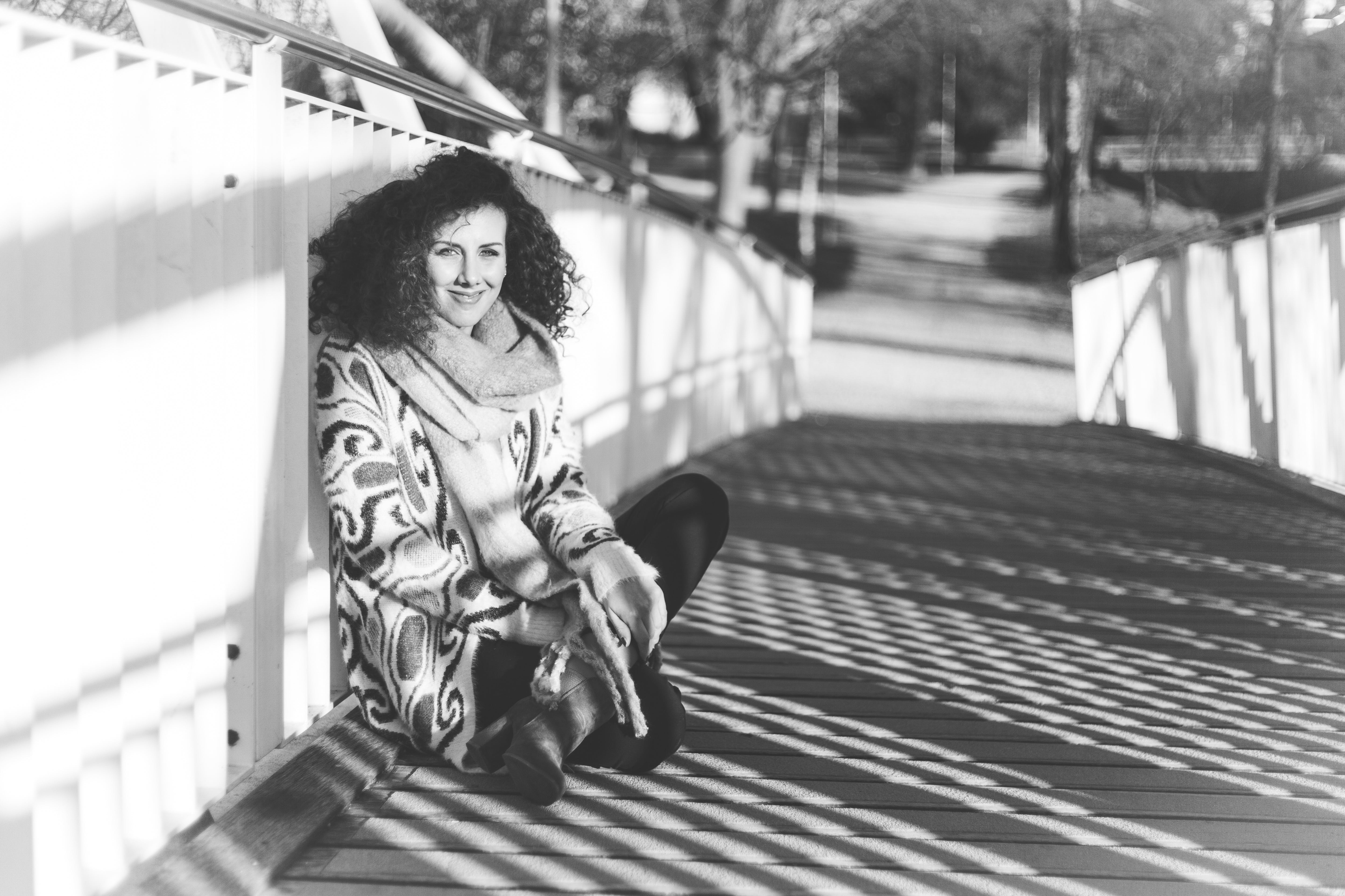 Grayscale Photography of Woman Sitting on Bridge