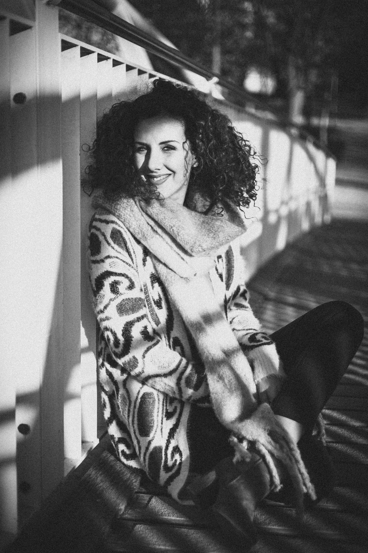 Grayscale Photo of Woman Sitting on Bridge