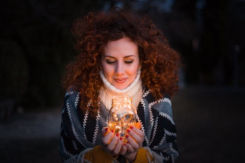 Woman Holding Clear Glass Jar Filled With Lights
