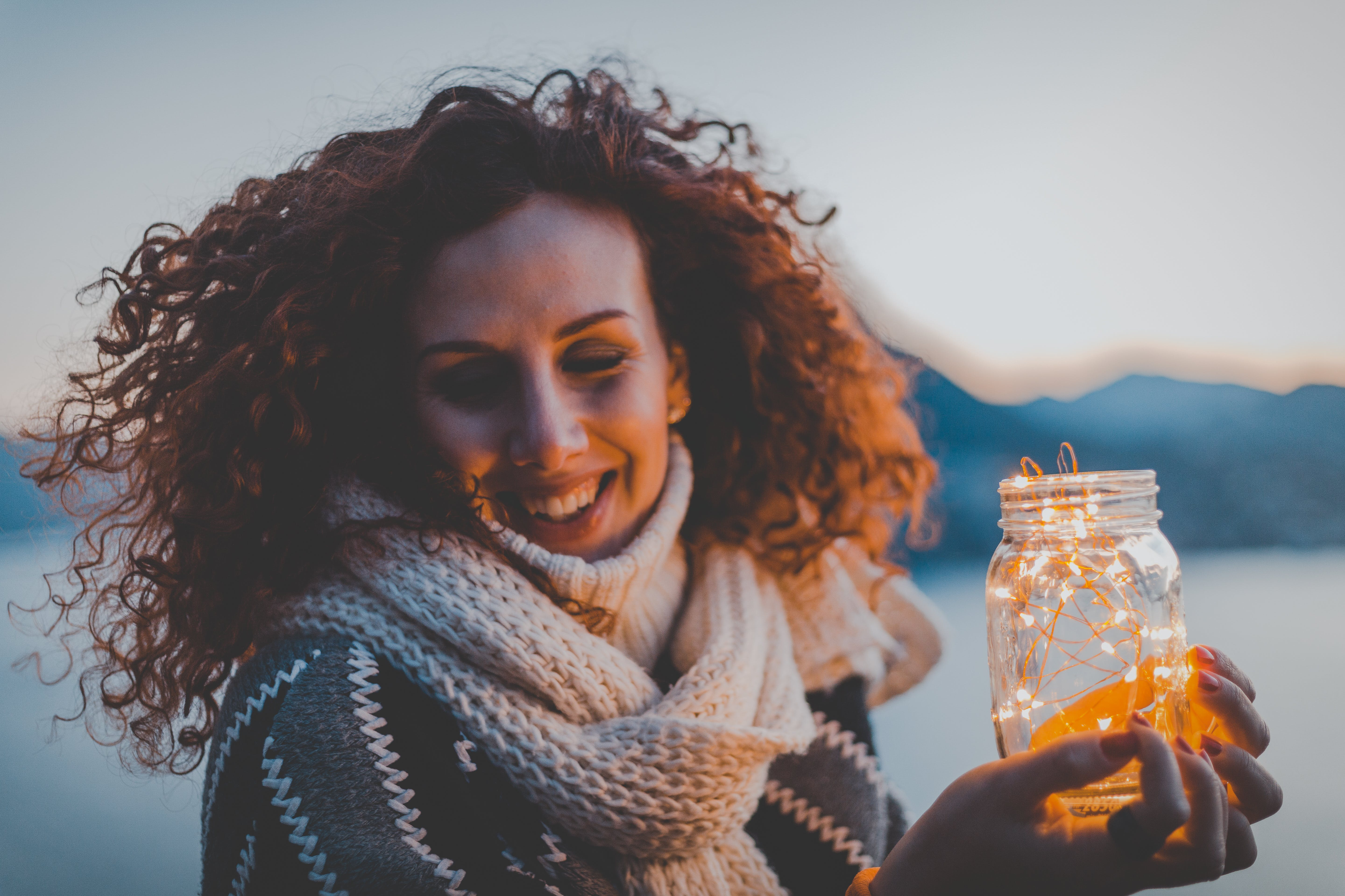 Woman Holding Lighted Jar Smiling