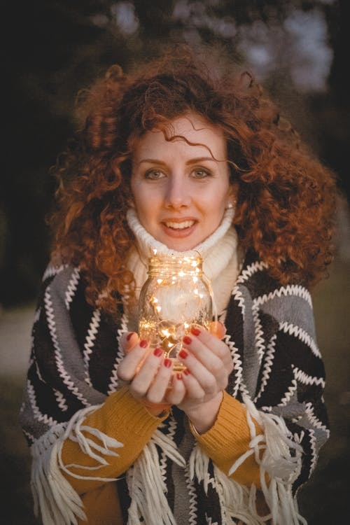 Woman Holding Clear Glass Jar With String Lights