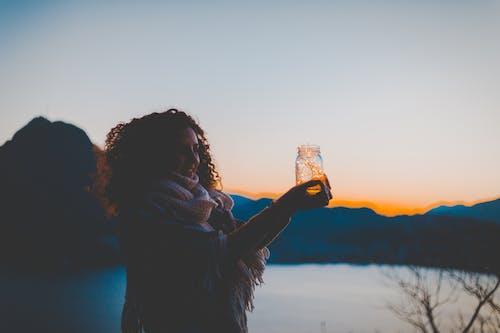 Frau, Die Einmachglas Mit Lichterkette Mit See Und Berg über Sicht Während Der Goldenen Stunde Hält
