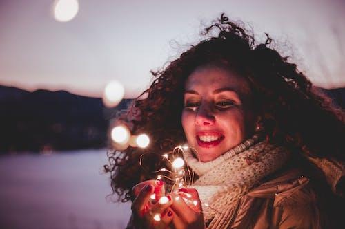 Gratis lagerfoto af halstørklæde, krøllet hår, kvinde, lys