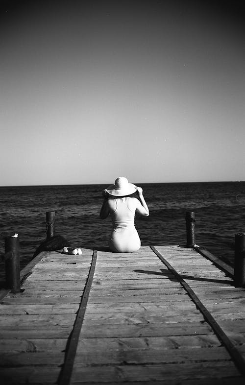 Woman Sitting on Wooden Dock with Sun Hat