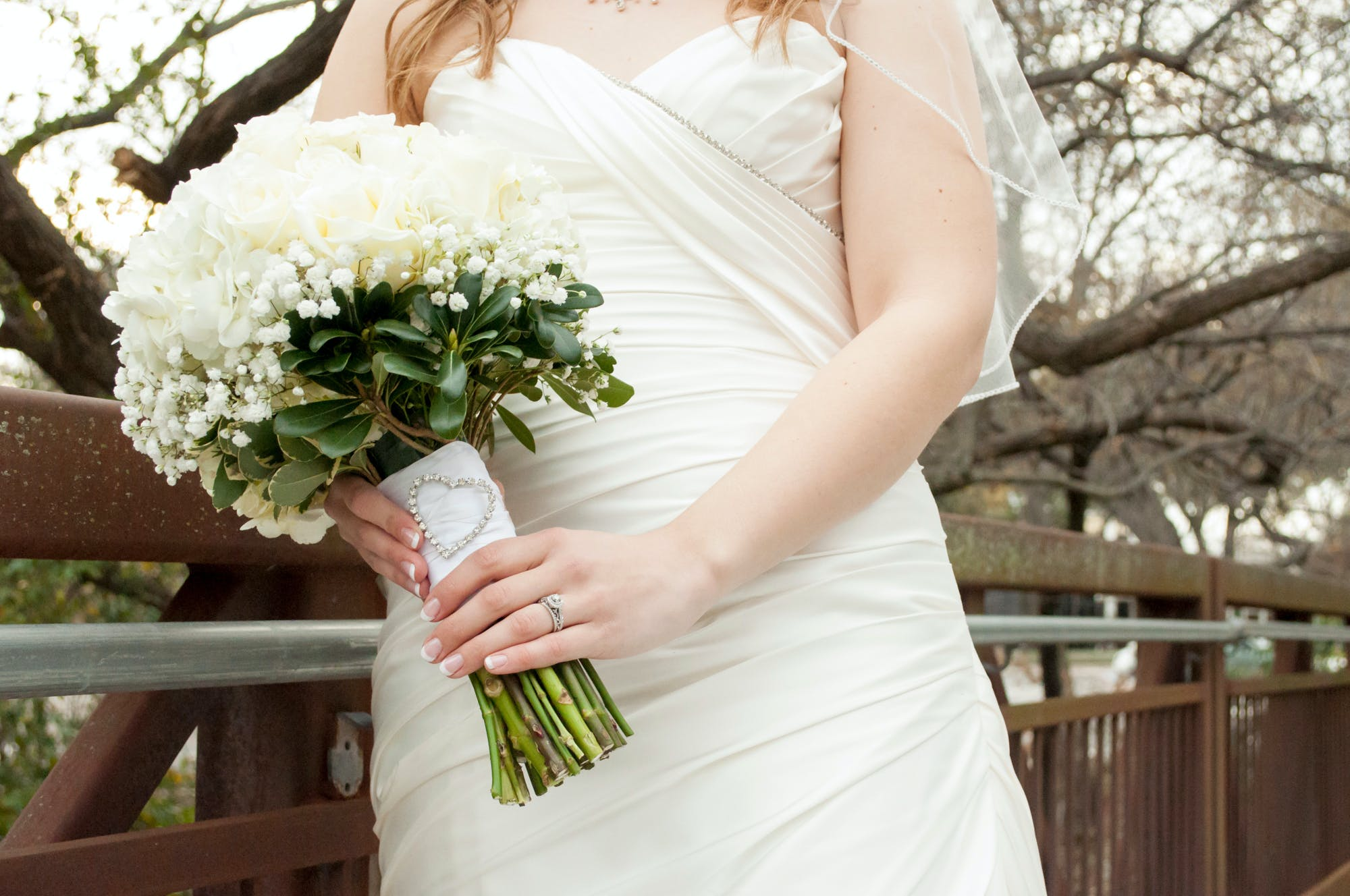 Woman Wearing White Wedding Gown While Holding Flowers