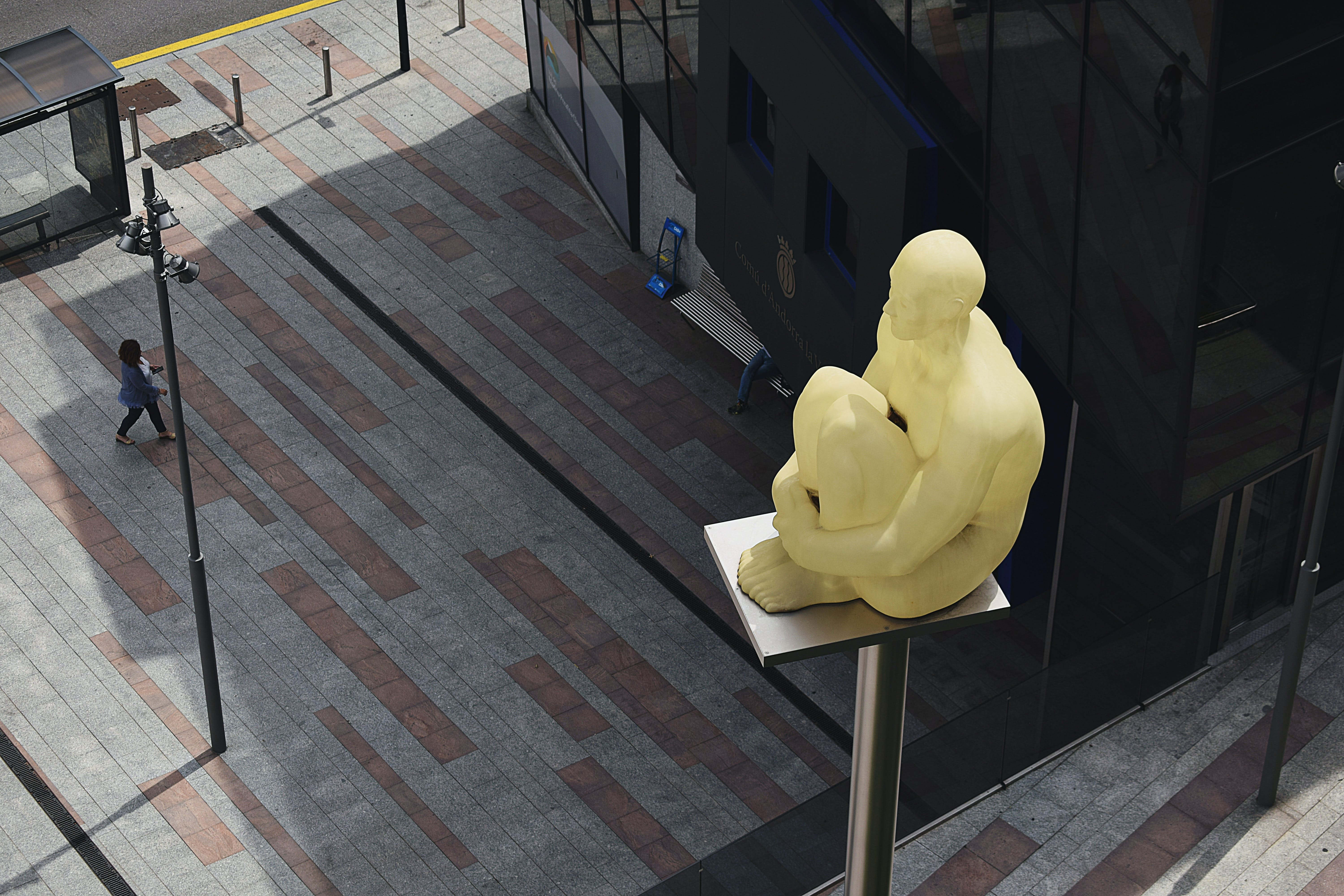Sitting Man Statue Placed on Gray Metal Post