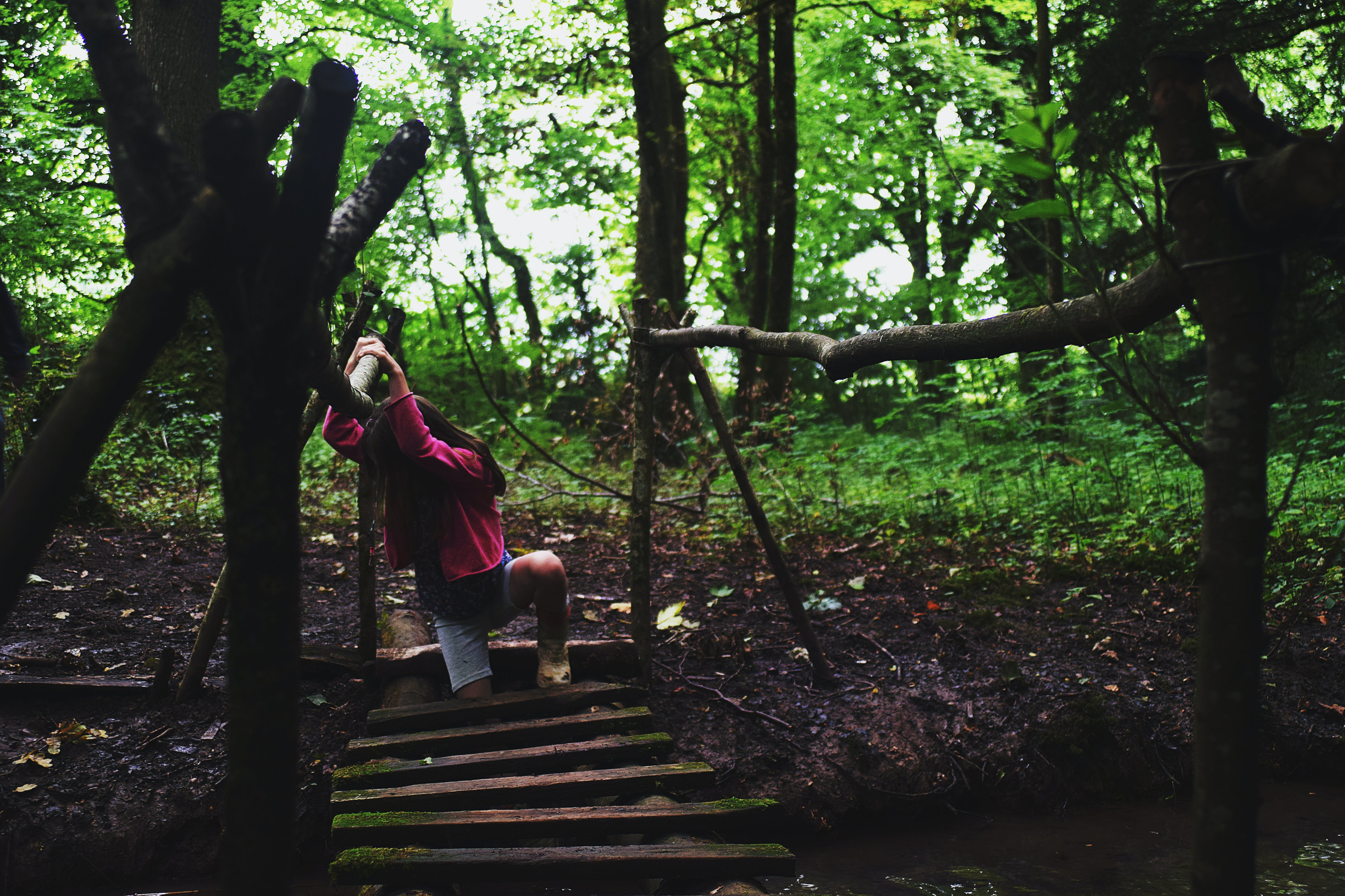 Girl in Pink Jacket on Wooden Bridge in the Forest