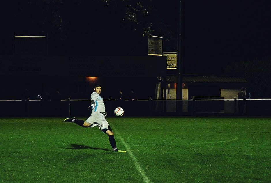 Person kicks soccer ball in field