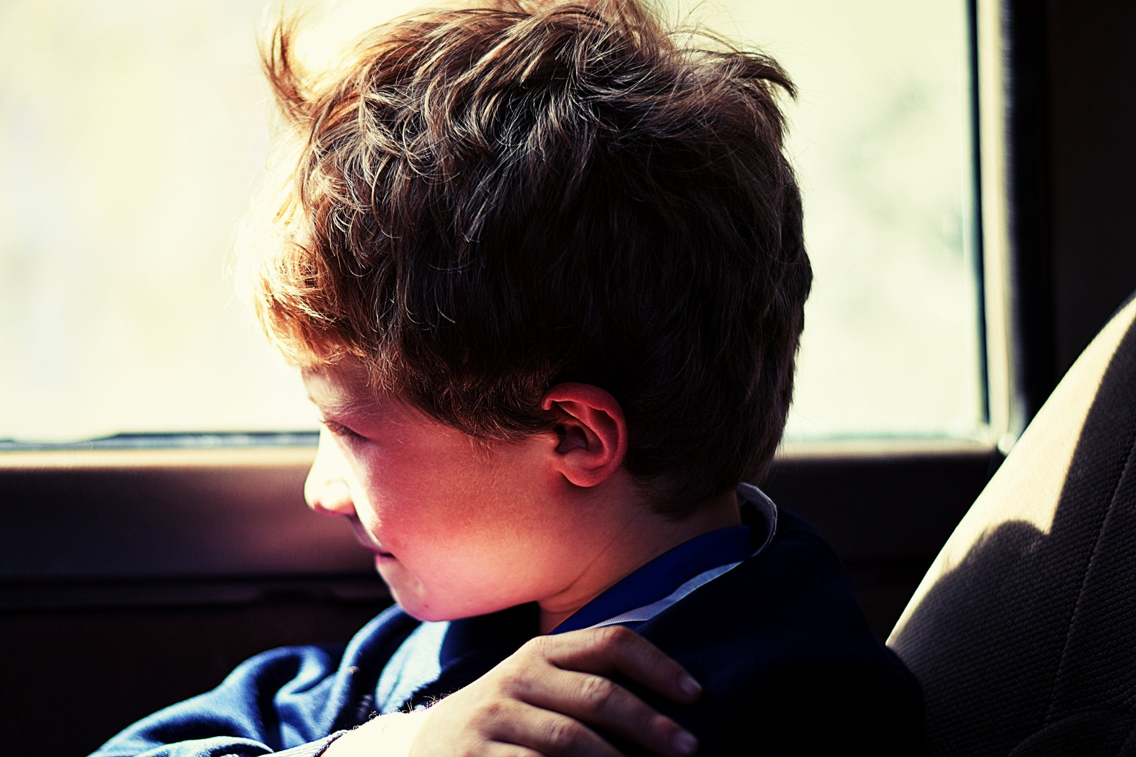 Boy in Blue Jacket Sitting Next to Vehicle Window