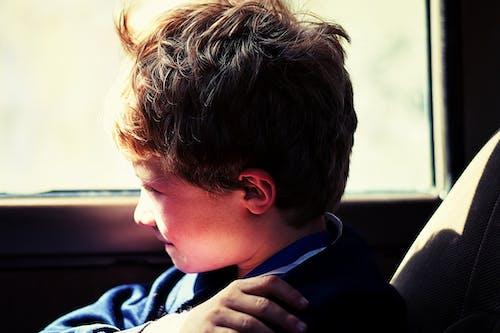 Boy in Blue Jacket Sitting Next to Vehicle Window