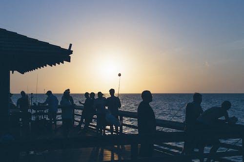 Zachód Słońca Nad Sylwetką Ludzi W Pobliżu Zbiornika Wodnego