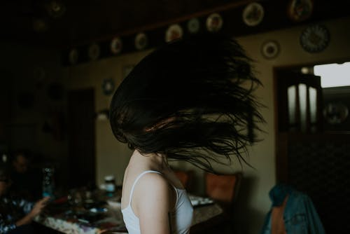 Woman in White Tank Top Flipping her Hair