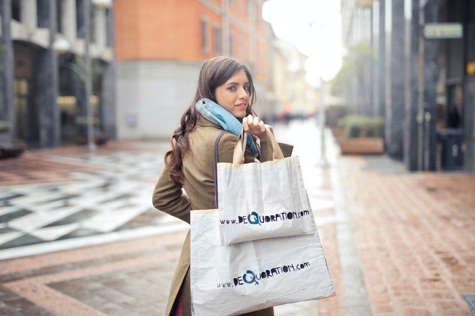Woman in Brown Coat Carrying Two White Tote Bags