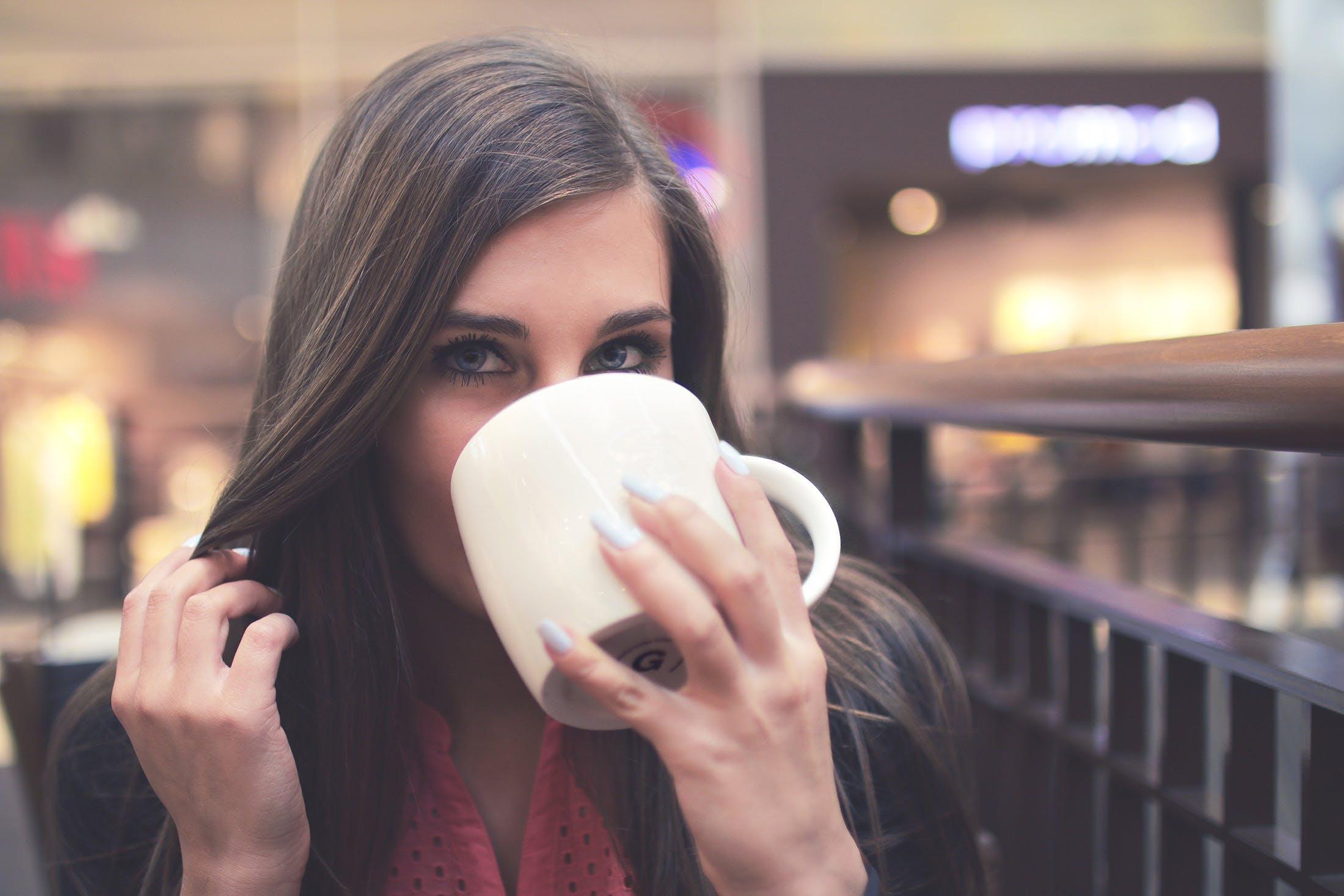 Woman in Black Mascara Drinking on White Ceramic Mug