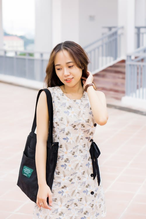 Woman in White and Black Floral Dress Holding Black Leather Sling Bag