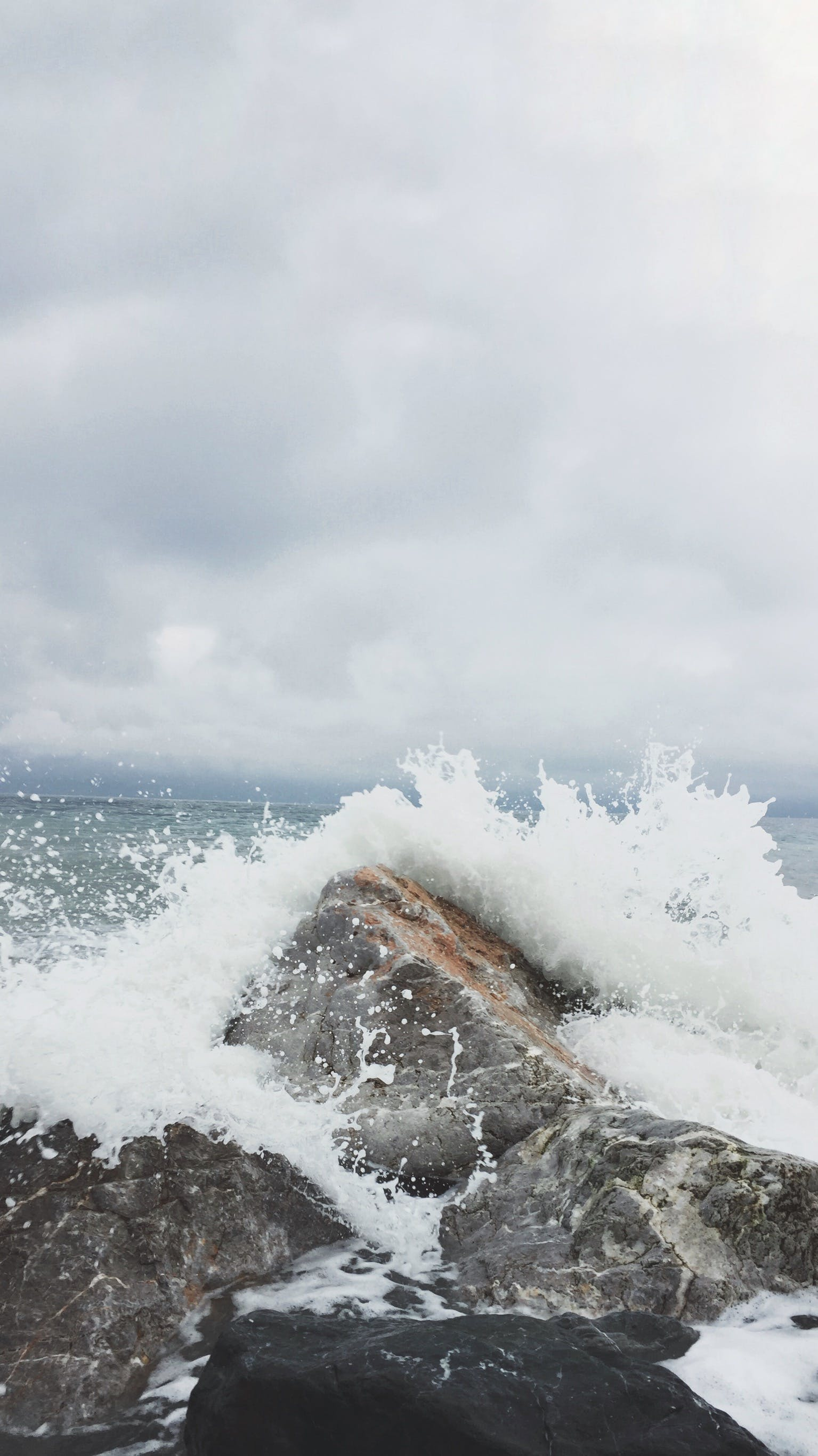Person Taking Photo of Sea Waves and Gray Concrete Rock