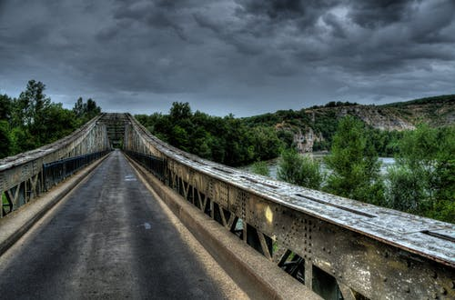 Bridge Beside Mountain Under Gray Clouds
