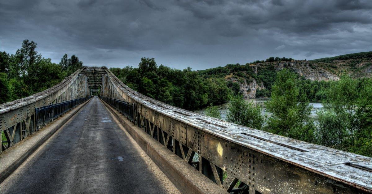 Bridge Beside Mountain Under Gray Clouds · Free Stock Photo