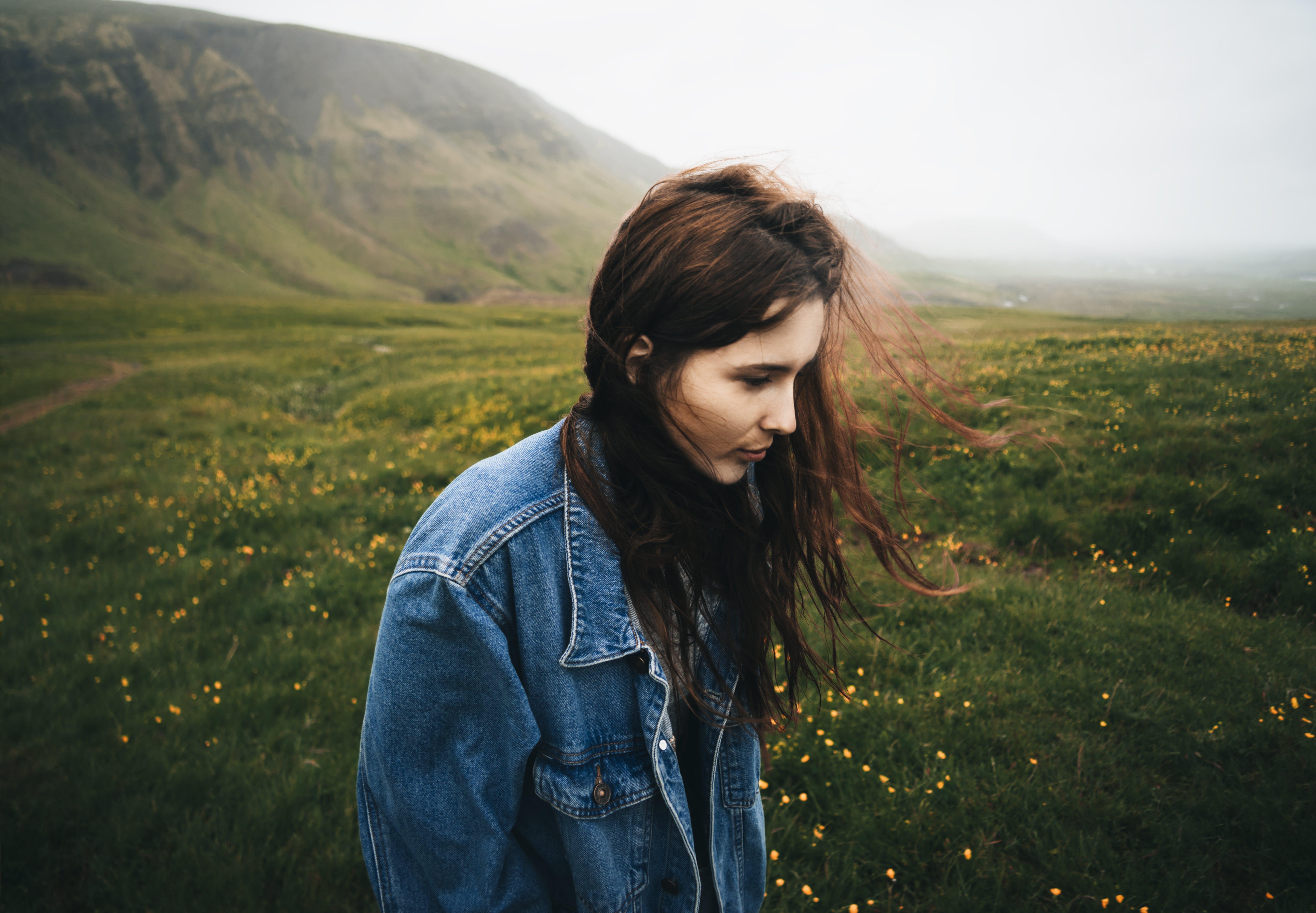 Woman Wearing Blue Denim Jacket Walking on the Green Grass Field