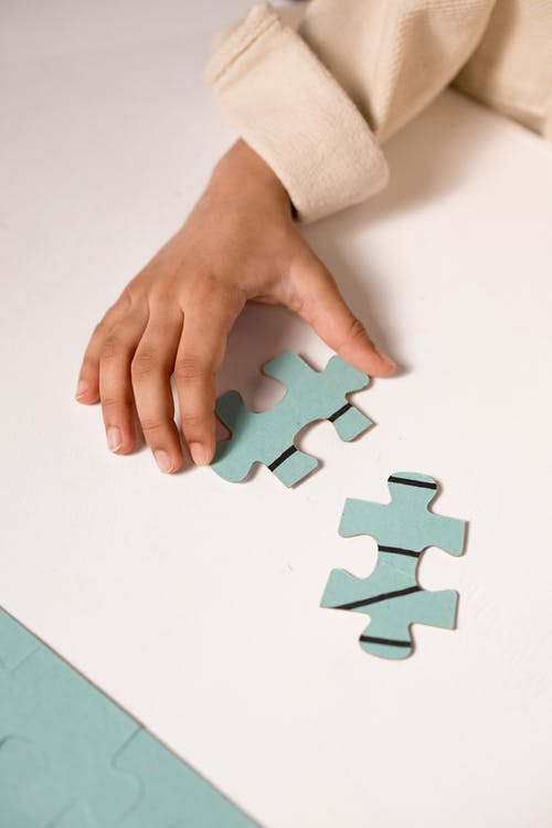 Person Holding Green Puzzle Piece