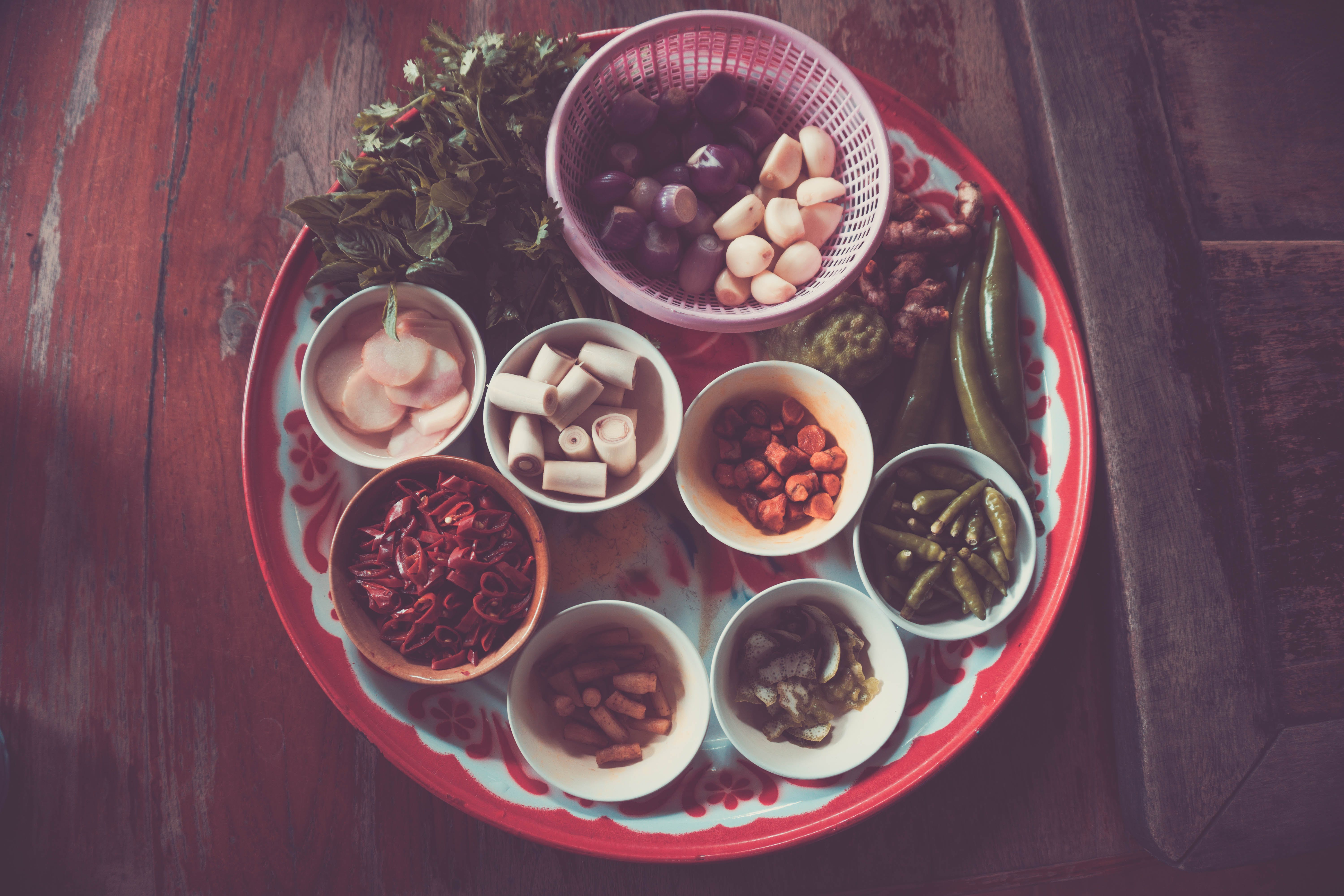 Assorted Spices on White and Red Plate on Brown Wooden Table