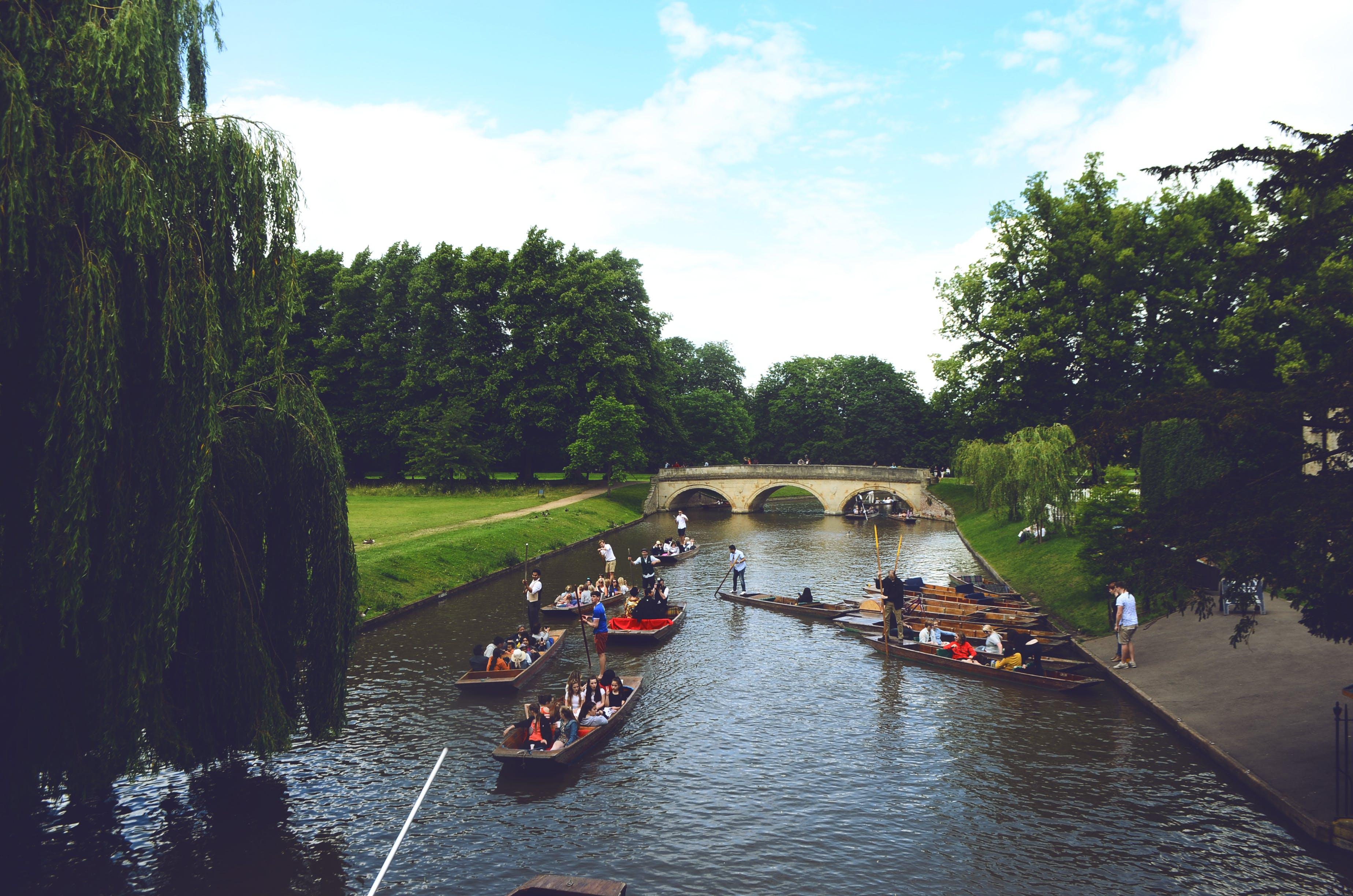 Group of People Ride on Jon Boats Near Bridge