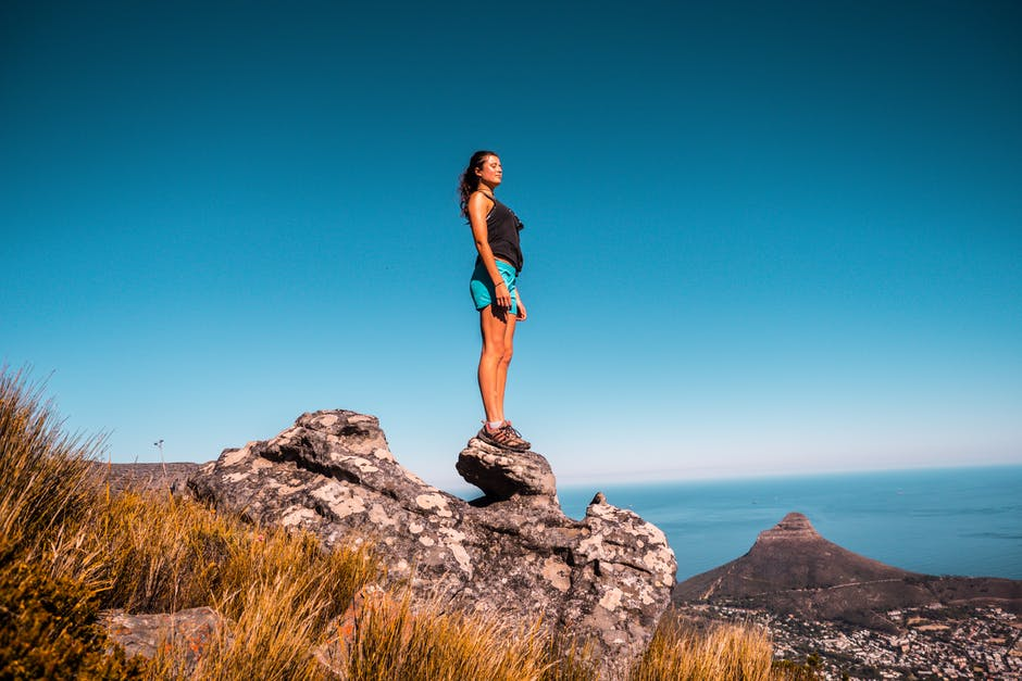 Woman in black top and blue shorts on stone under blue sky