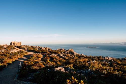 Безкоштовне стокове фото на тему «берег моря, блакитне небо, вода, гора»