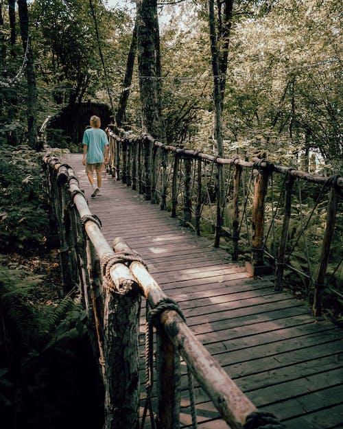 Woman in White Shirt Walking on Wooden Bridge