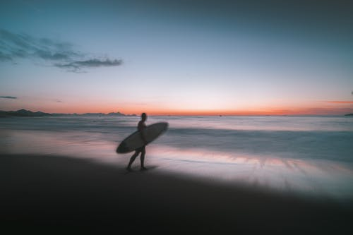 Person Holding White Surfboard Walking on Beach during Sunset