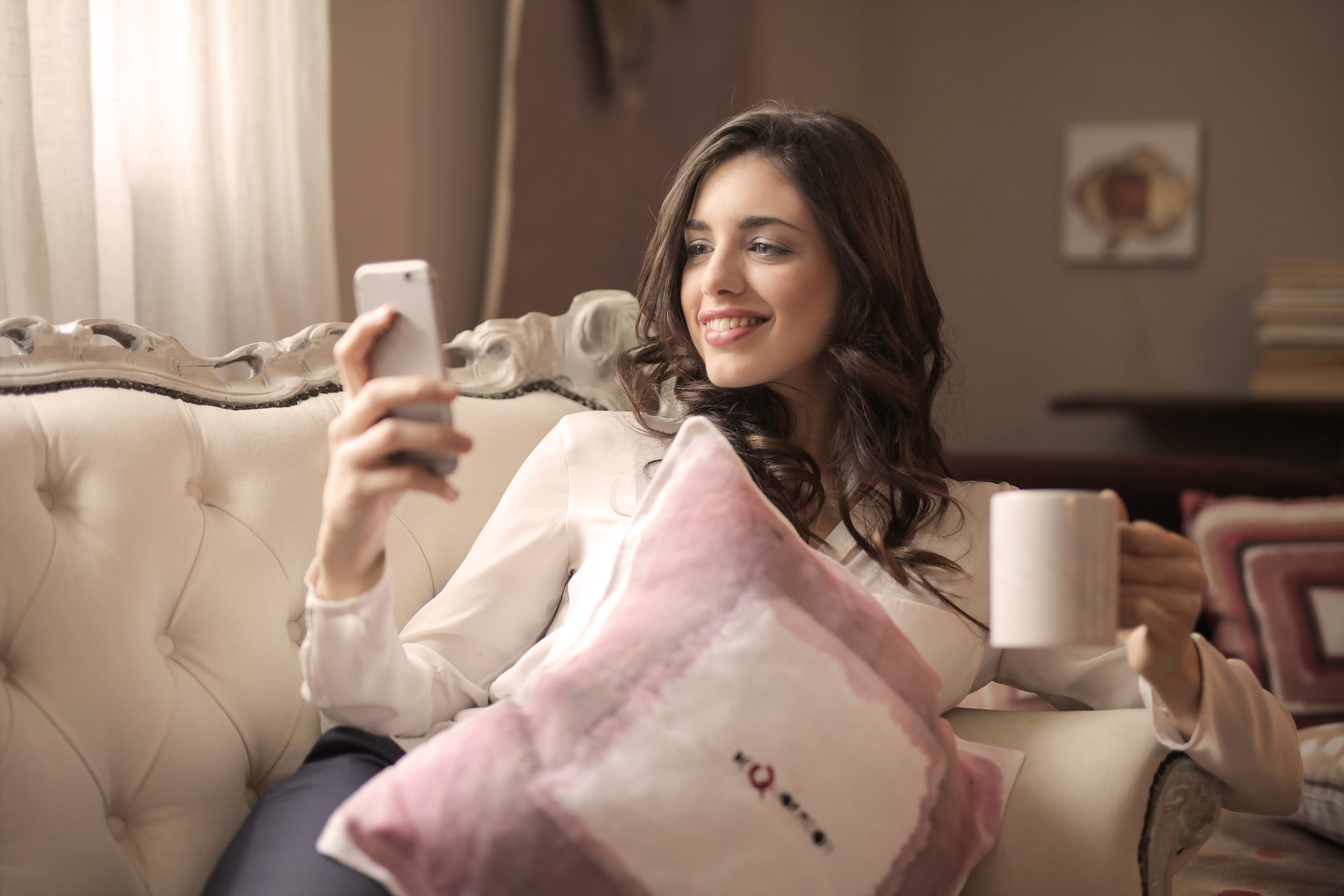Woman in White Long-sleeved Shirt Holding Smartphone Sitting on Tufted Sofa