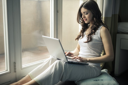 Woman Wearing Tank Top Sitting by the Window