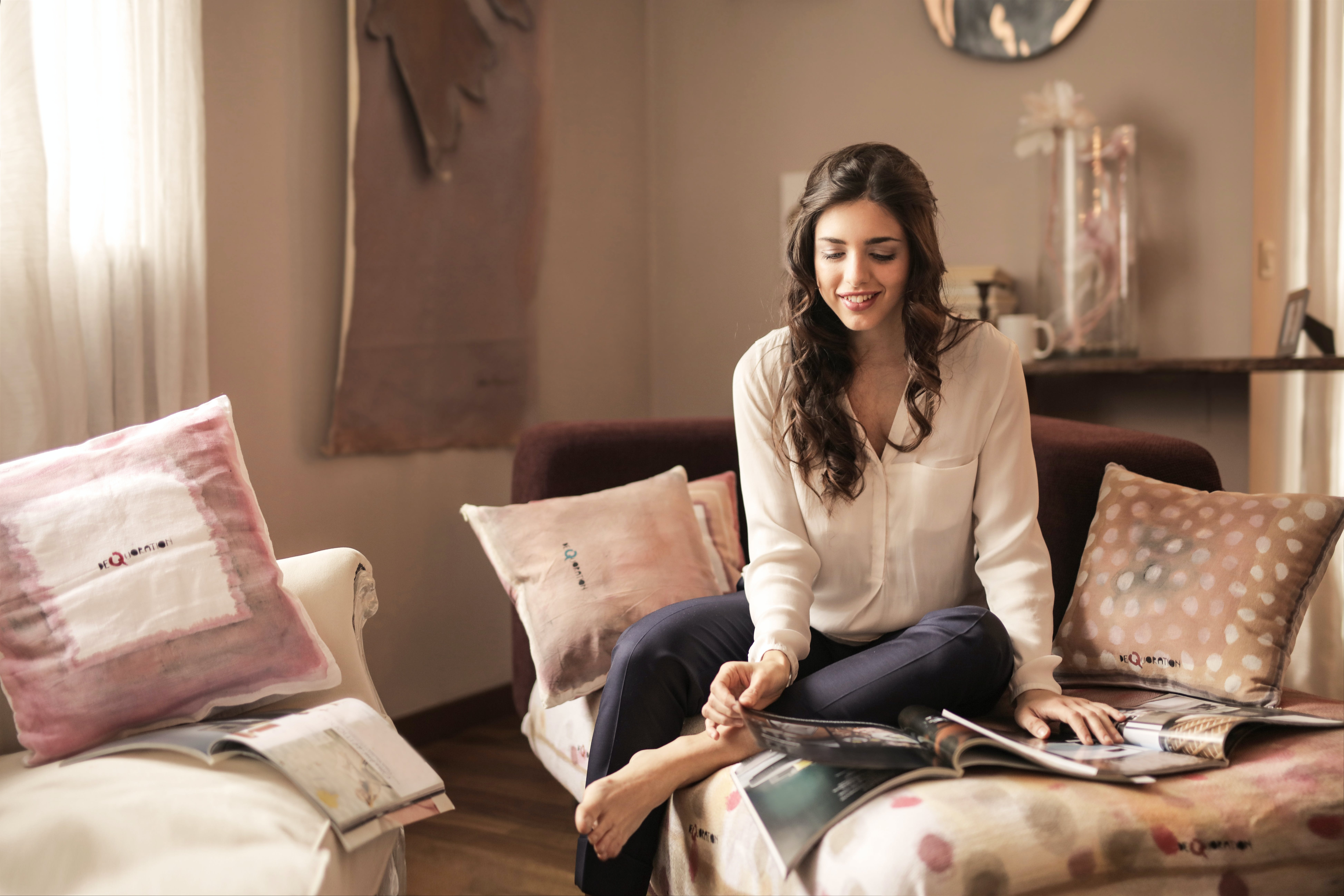 Women in White Button-up Long-sleeved Top and Black Pants Sitting on White and Brown Bed