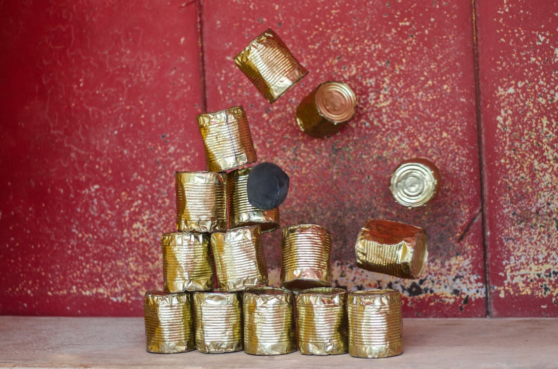Pile Brass-colored Cans on Beige Surface