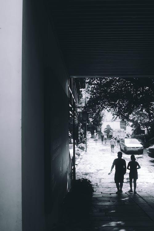 2 Men Walking on Sidewalk
