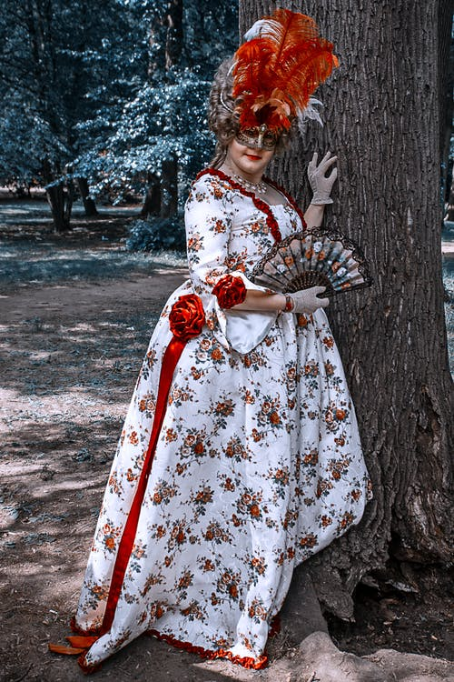 Woman in White Red and Green Floral Dress Holding Black and White Striped Scarf