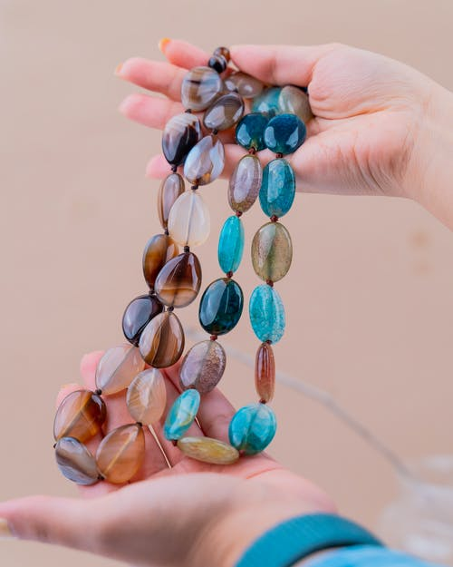 Person Holding Colored Beaded Accessories