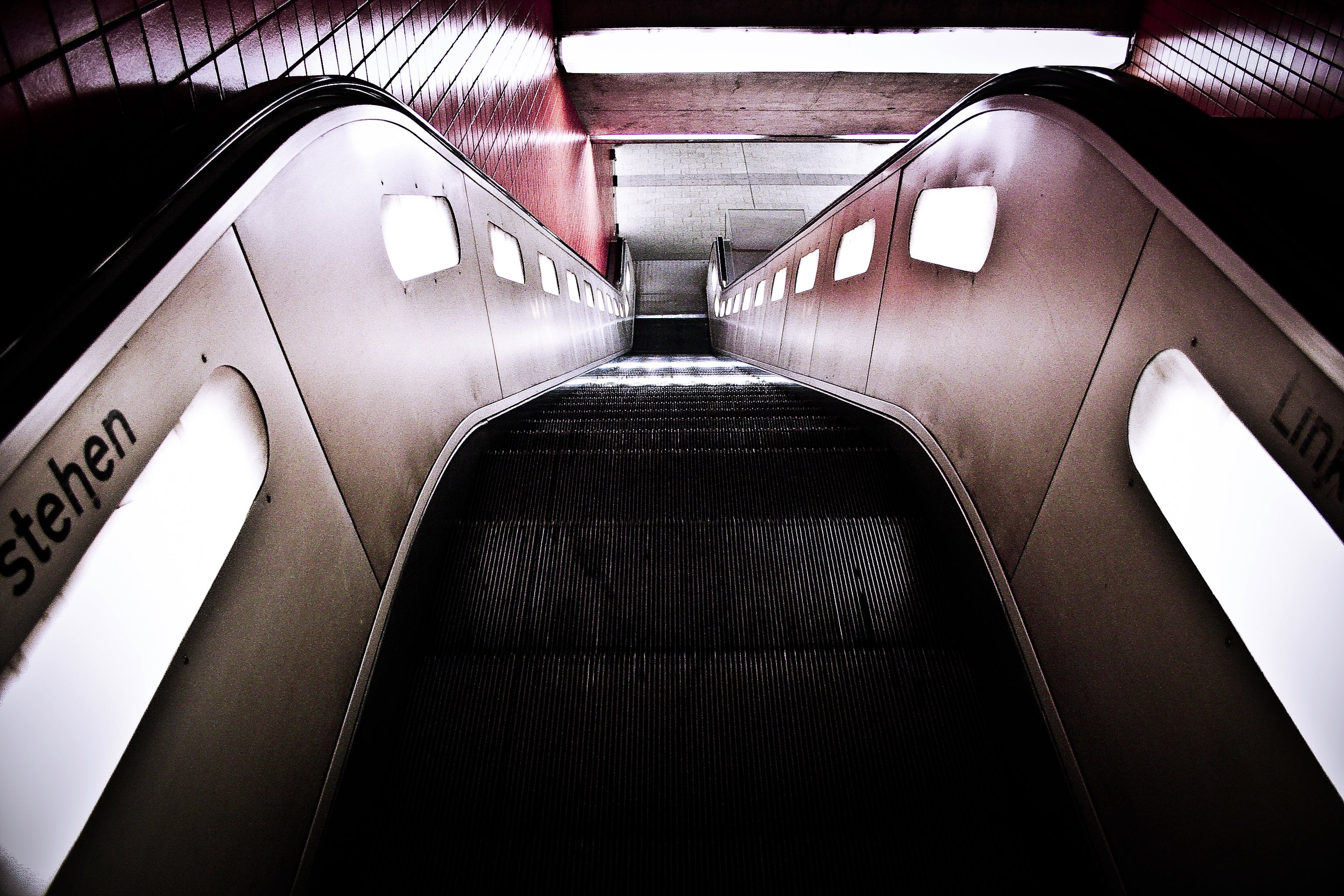 Black Escalator Near Red Wall Tiles