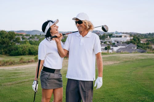 Man and Woman with Golf Clubs Smiling in Golf Course