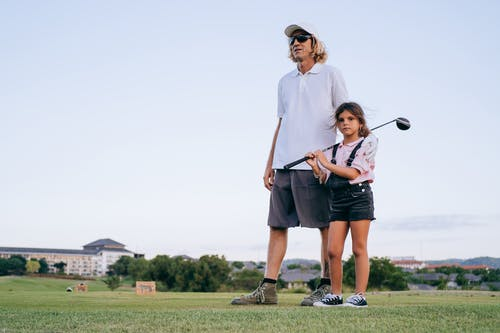 Man with Girl Holding Golf Club Standing on Grass Field